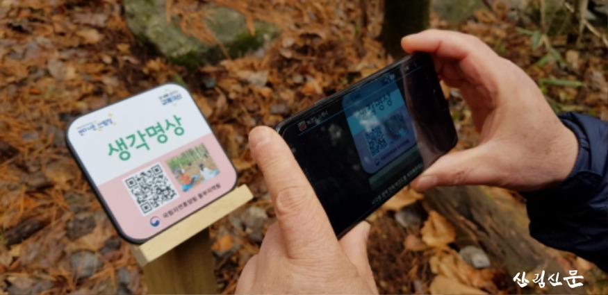 (사진 2) 휴대폰으로 안내판에 있는 QR코드를 스캔하는 모습입니다..jpg
