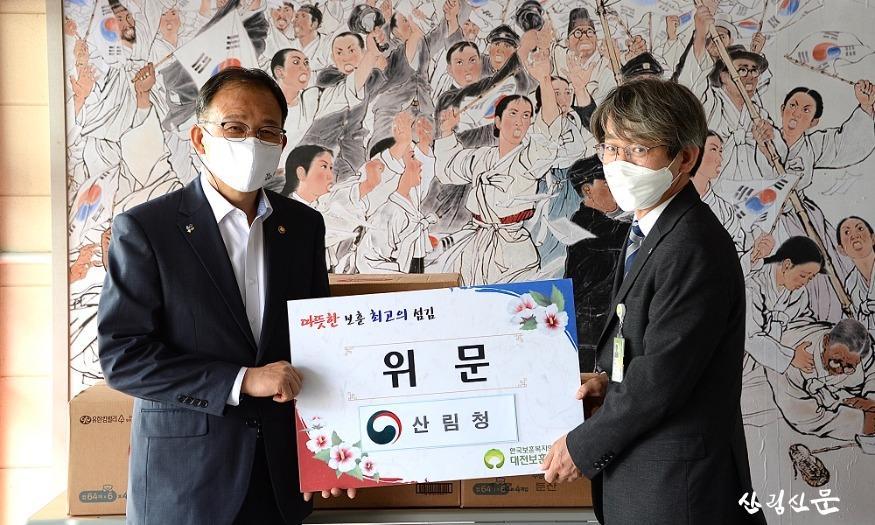 사진3_박종호 산림청장(왼쪽)이 대전보훈요양원 원장  김주천(오른쪽)에게 위로 물품을 전달하고 있다..jpg